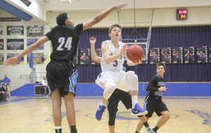 Photo by Jesus Sepuvelda Clovis High's No. 5 CJ Sells flies in for a layup as Clovis North junior No. 24 Elijah Straughter defends on the play in a game won by the Broncos 74-50 on Friday, February 5.